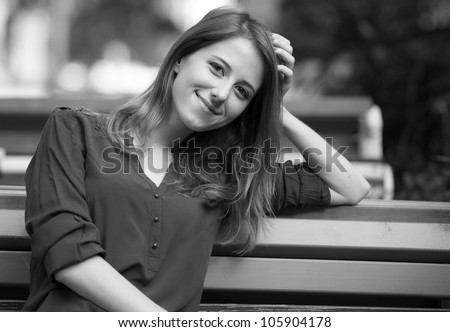 Style girl sitting on the bench in the cafe. Photo in black and white style. - stock photo