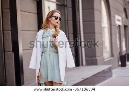 Style girl walks through the summer city among fashion boutiques in white jacket and mint color dress and dark sunglasses  - stock photo