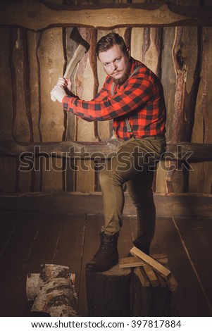 Style lumberjack. Woodcutter with a beard and mustache, wearing a red shirt, pants and suspenders with an ax on a wooden background. Modern style. Serious lumberjack swung an ax - stock photo