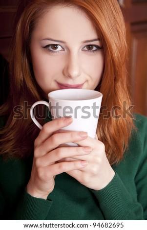 Style redhead girl drinking coffee near wood doors. - stock photo