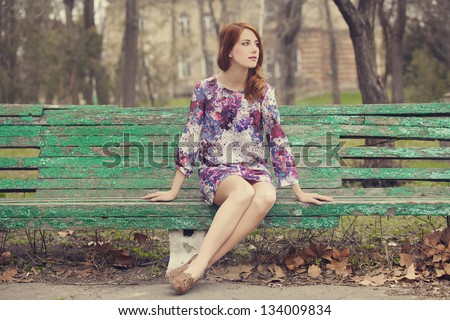 Style redhead girl sitting on the bench - stock photo