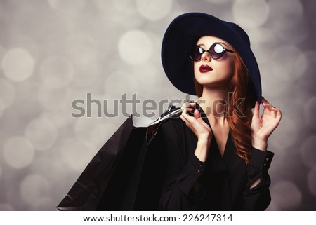 Style redhead girl with sunglasses and shopping bags. - stock photo