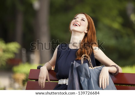Style redhead women sitting on the bench with shopping bags - stock photo