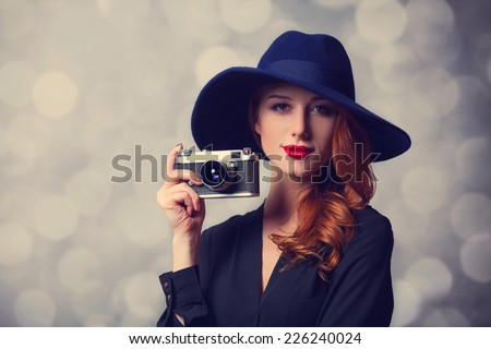 Style redhead women with sunglasses and vintage camera. - stock photo