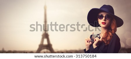 Style redhead women with sunglasses and vintage camera on Paris background - stock photo
