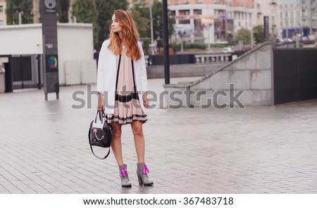 Style tall girl with dark long hair flowing in the wind walking in the city in short summer  pale pink dress and white jacket with black bag and grey boots - stock photo