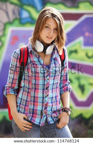 Style teen girl with backpack standing near graffiti wall. - stock photo