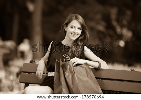 Style women sitting on the bench with shopping bags - stock photo