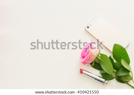Styled desktop scene  with  mobile and pink flowers, copy space on white table - stock photo
