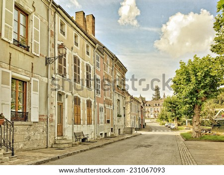 Styled photo of a traditional street in center of Fumay in Ardenne, France, with buildings from 17-18 centuries. Vintage look effects applied