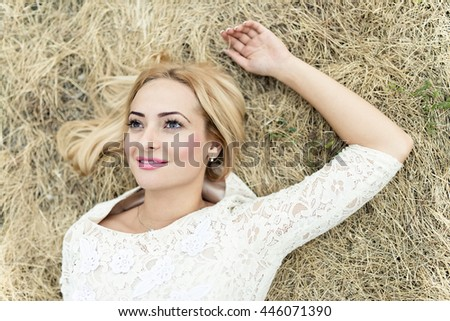 Styled portrait of beautiful young woman in the hay - stock photo