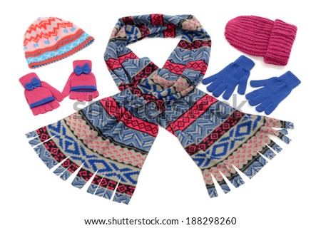Styling a scarf with different accessories. Pink and blue winter accessories isolated on white background. Cute wool scarf, gloves and hats nicely arranged and matching. - stock photo