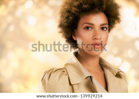 Stylish African-American woman posing in front of a glittering gold background. - stock photo