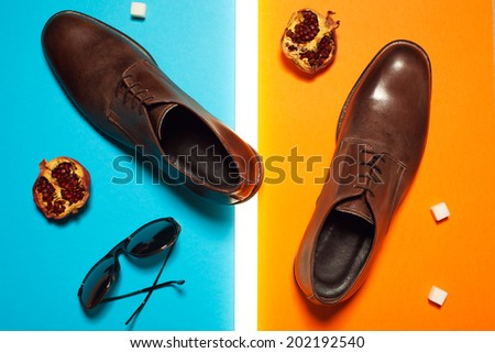 Stylish and arty hipster fashion concept in avant-garde style. Trendy eyewear and leather shoes on blue and orange background with pomegranates, sugar cubes and white neon lamp. Studio shot - stock photo