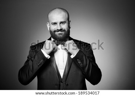 Stylish and brutal bald man with a beard in elegant black suit