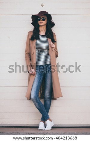 Stylish and confident. Full length of beautiful young woman in sunglasses looking away while standing against wall outdoors  - stock photo