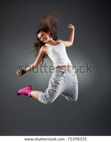 stylish and cool looking break dancer jumping in studio