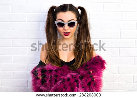 Stylish and sexy. Young girl in sunglasses looking directly at the camera in a black top and a purple fur coat, long hair tied in a ponytail on a background of white brick wall, ready for party. - stock photo