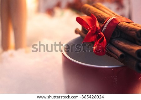 stylish aromatic cinnamon sticks on red cup on white background, seasonal greetings