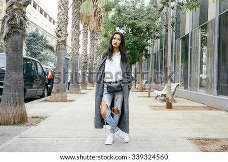 stylish Asian young woman posing in the city streets