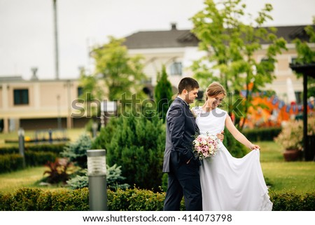Stylish attractive happy bride and handsome groom lovely hugging outdoors and looking away. Copyspace at the left. Beauty bride with groom. Cute lady and handsome guy - stock photo