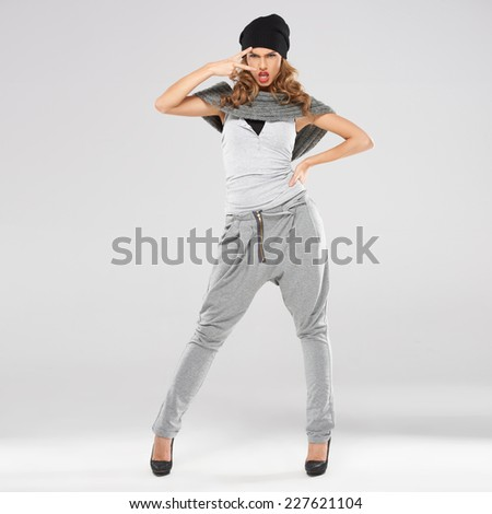 Stylish attractive trendy young woman with an attitude posing with her hand on her hip giving a peace or victory v-sign with a cute expression  on grey - stock photo