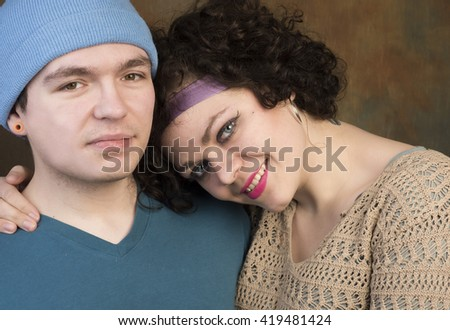 Stylish, attractive young Caucasian couple sharing an affectionate moment against a portrait background - stock photo