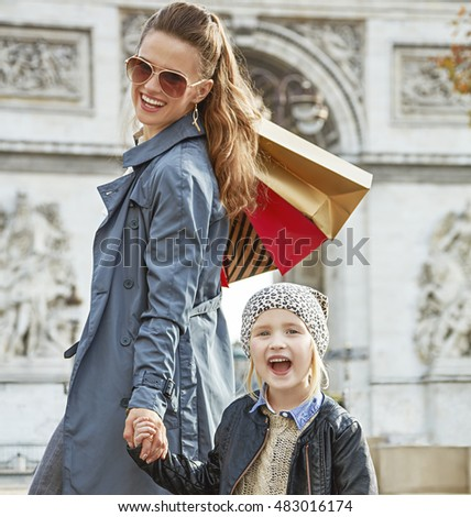 Stylish autumn in Paris. smiling trendy mother and child with shopping bags near Arc de Triomphe in Paris, France
