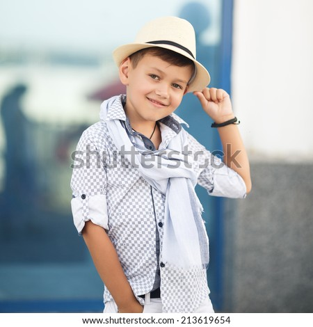 stylish baby boy having fun outside in the park. Cute happy boy child outdoors. cute little stylish boy in classic style in the city. Happy child posing outdoor. - stock photo