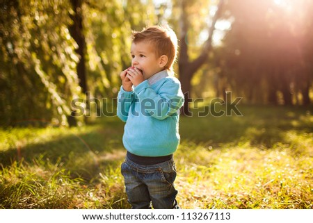 stylish baby boy having fun outside in the park,eating apple