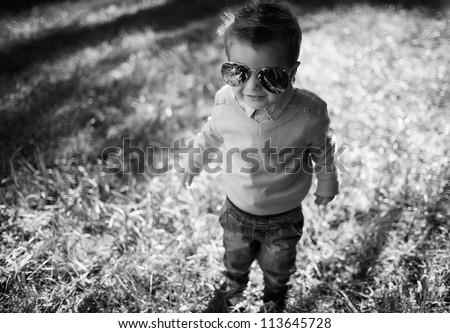 stylish baby boy having fun outside in the park,wearing  glasses
