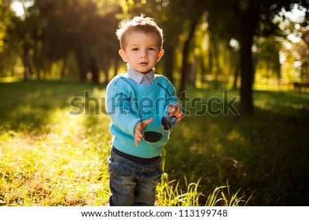 stylish baby boy having fun outside in the park,with glasses - stock photo