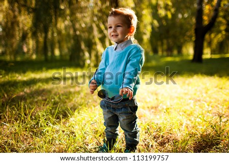 stylish baby boy having fun outside in the park,with glasses