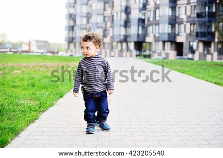 Stylish  baby boy in jeans  walking in the city - stock photo