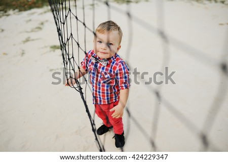 stylish baby boy on background volleyball net. child in red checkered shirt with a tie and a butterfly in red jeans on the background of sports field