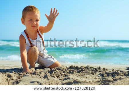stylish baby boy waving hand on the beach - stock photo