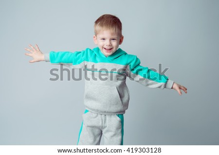 Stylish baby boy with blond hair in the sports suit. He poses on a grey background. Sporting style. Studio shot - stock photo