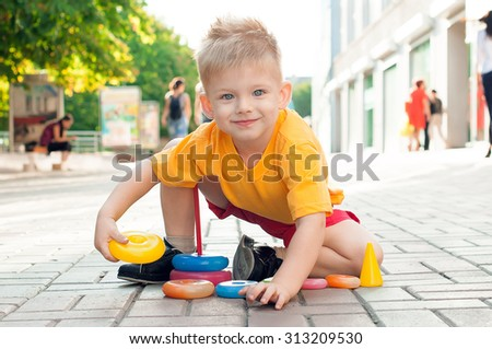 Stylish baby boy with blond hair in the yellow t-shirt and in red shorts. He sits near a shopping center and plays with a pyramid. Hipster style. Sunny weather. Outdoor shot - stock photo