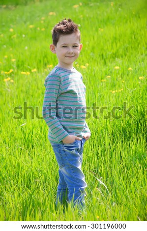 Stylish baby boy with dark hair and in a striped polo-neck, pose  in the  green meadow. Hipster style. Sunny weather. Outdoor shot - stock photo