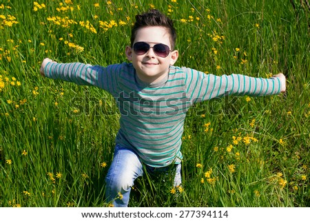 Stylish baby boy with dark hair in  striped polo-neck and in trendy sunglasses. Smile. Hipster style. Outdoor shot