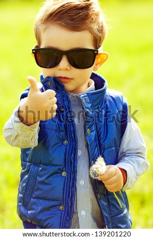 Stylish baby boy with ginger (red) hair in trendy sunglasses and blue jacket standing in the park, holding dandelion and showing thumb up (ok). Hipster style. Sunny weather. Outdoor shot