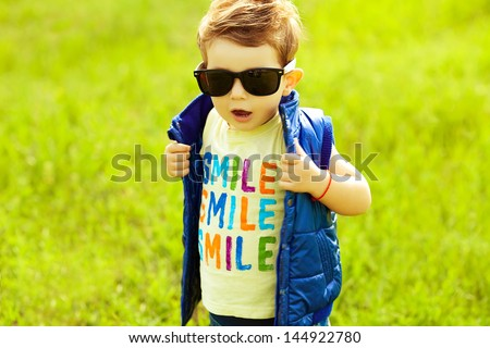 Stylish baby boy with ginger (red) hair in trendy sunglasses and blue jacket standing in the park. Hipster style. Sunny weather. SMILE word printed on t-shirt. Copy-space. Outdoor shot - stock photo