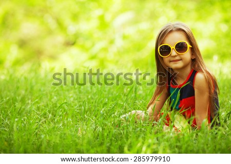 Stylish baby girl with long light brown hair in trendy sunglasses and avant-garde style dress sitting in the park and smiling. Hipster style. Sunny weather. Copy-space. Outdoor shot - stock photo