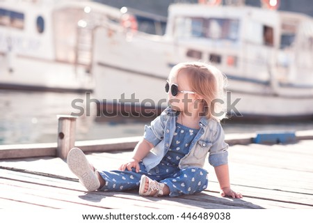 Stylish baby girl 2-3 year old wearing trendy denim clothes sitting on wooden sea pier outdoors. Looking away. Childhood. - stock photo