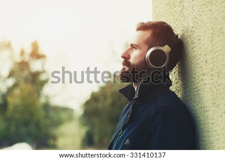 stylish bearded man  in headphones listening to music