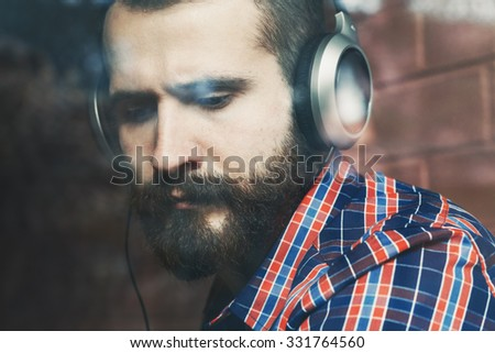stylish bearded man  in headphones listening to music near window with reflection - stock photo
