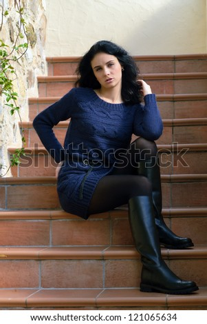 Stylish beautiful girl sits on the stairs near rough stone wall of the old house. Tuscan, Italy - stock photo