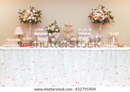 Stylish beautiful luxury sweet candy bar set  on the table at the wedding ceremony in restaurant. Flower rose bouquet and tasty desserts on the table. Confectionery business concept.