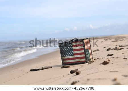 Stylish beautiful vintage suitcase with coloring in the form of the American flag Stars and Stripes stands on the sea