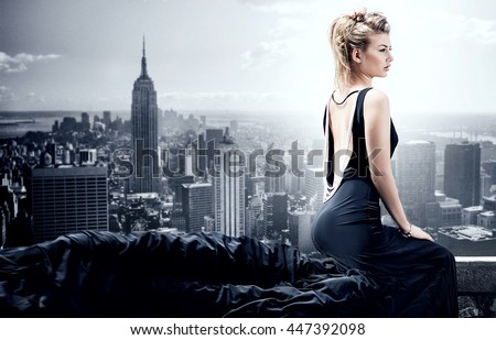 Stylish beautiful woman posing in black elegant dress. Skyline on background. - stock photo
